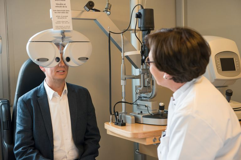 Female optometrist examining mans eyes
