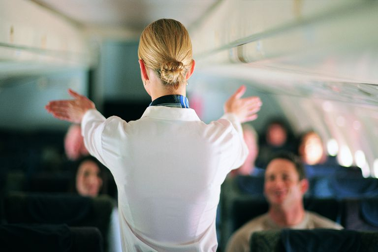 A flight attendant explains safety procedures to passengers