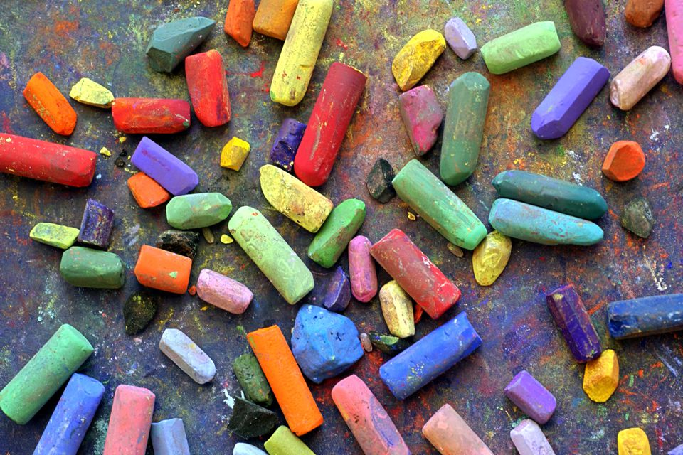 Close-up still life of colorful chalk on black surface.