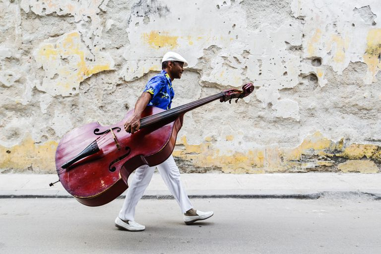 Hispanic musician carrying bass on city street