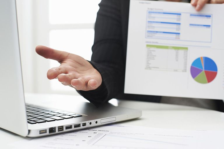 man presenting data in front of laptop