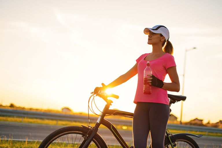 Woman with bicycle on side of road