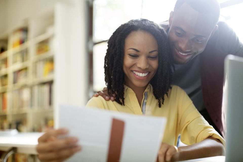 African American couple looking at paper with an open laptop