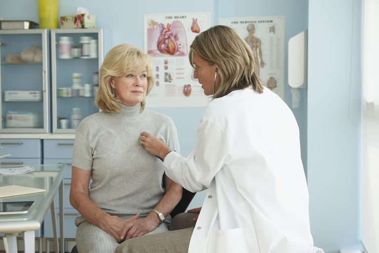 doctor using stethoscope on female patient