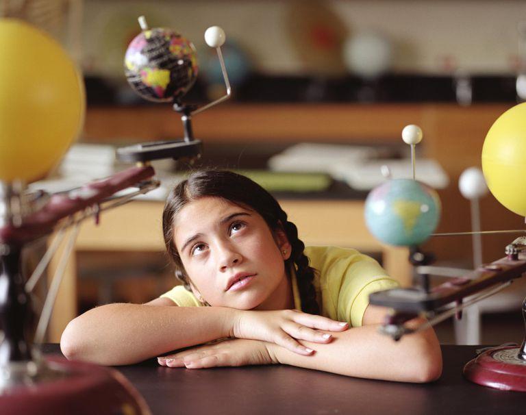 Girl (9-11) looking at model of Earth orbiting around sun.