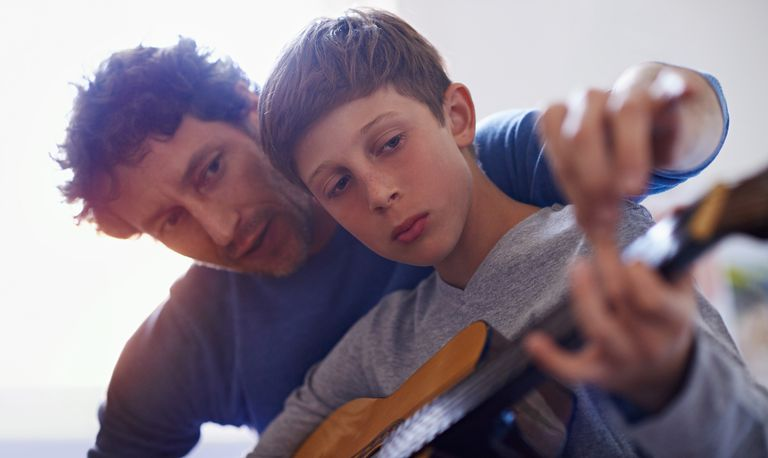 boy learning guitar with his father