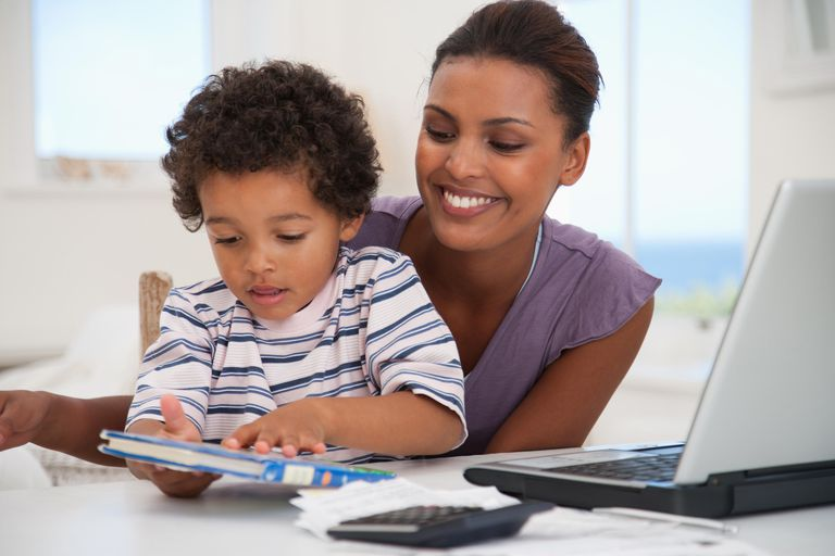 Mother and son with book and laptop