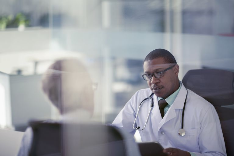 Doctor talking with patient at desk in office