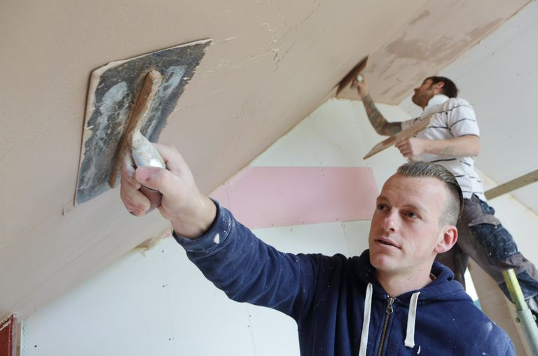 Two male builders plastering house interior