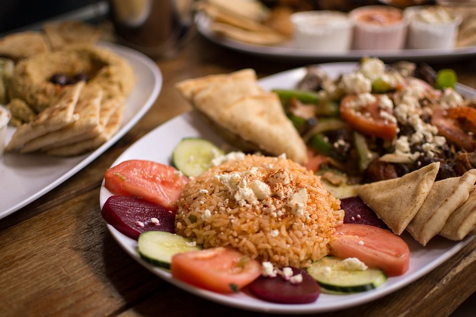 Greek plate of rice, hummus, pita bread, vegetables