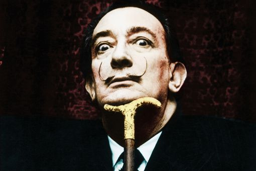 Portrait of artist Salvador Dali with large mustache, resting his head on a cane