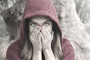 Frightened woman wearing red hood covering face with her hands