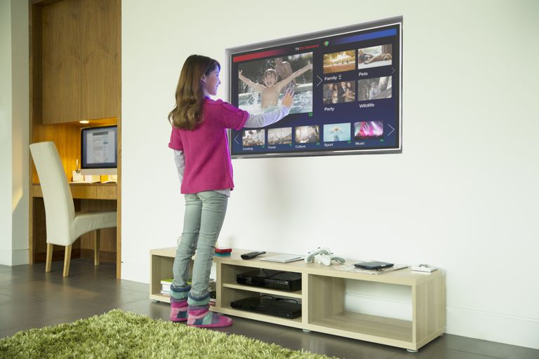 Girl using touch screen television in living room