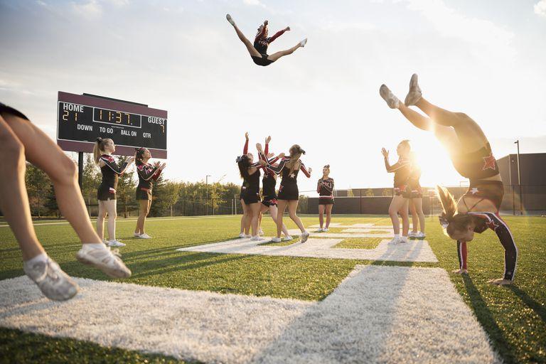 Teenage girl high school cheerleading team performing double nine jump on sunny football field