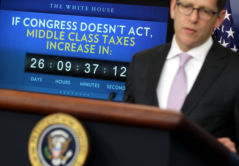 White House press secretary standing in front of sign about middle class taxes