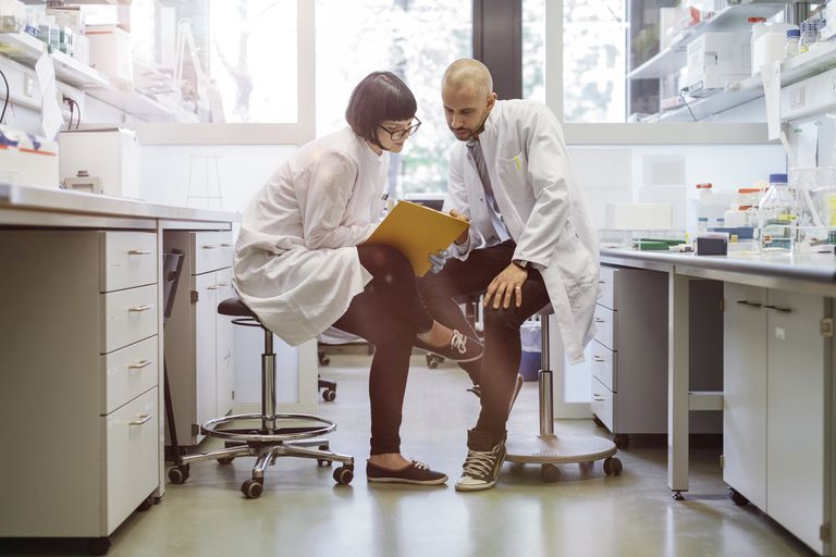 Two scientists inside a laboratory discussing