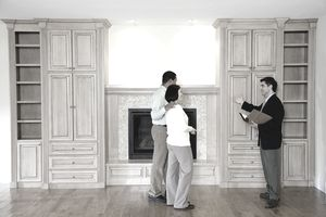 Male real estate agent showing living room to couple