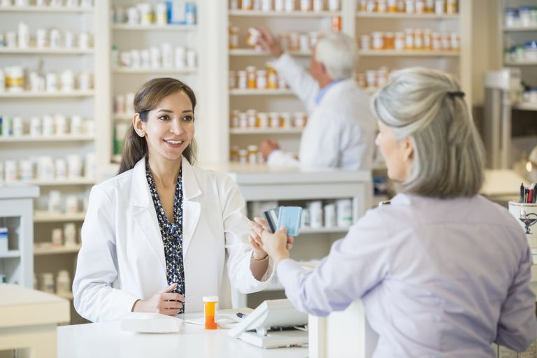 Woman paying at a pharmacy counter.