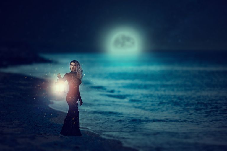 Woman walking on the beach during the full moont