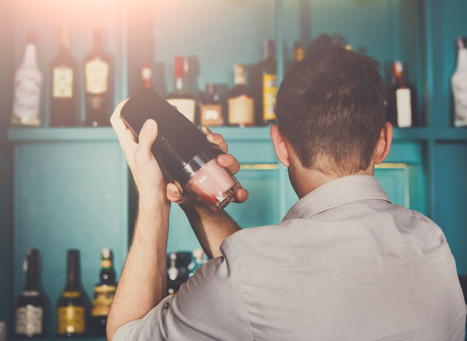 Young male bartender shaking a cocktail in a Boston cocktail shaker.