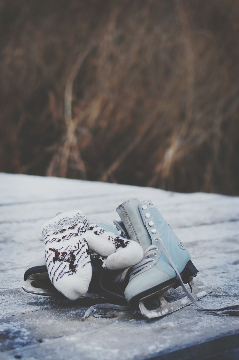 A pair of ice skates and mittens on an icy pond.