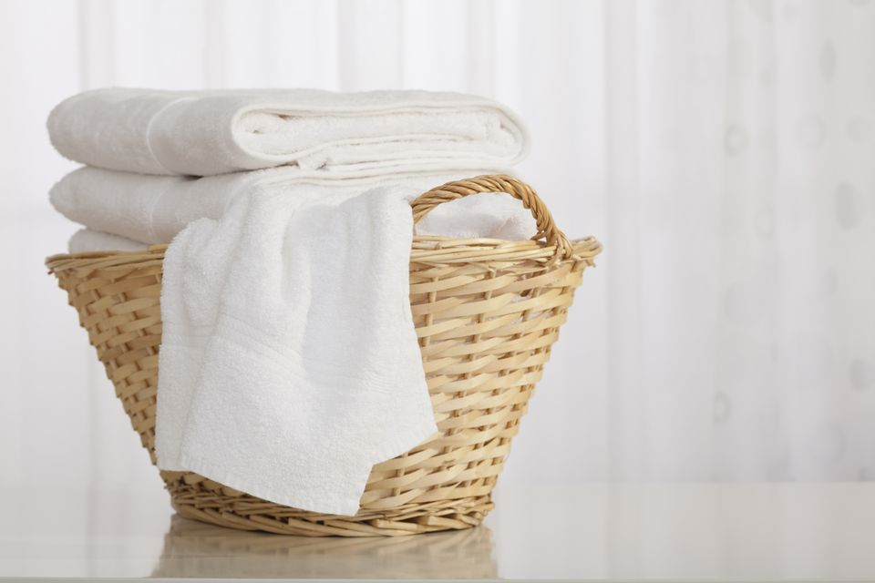 Studio shot of stack of white towels in Wicker Basket