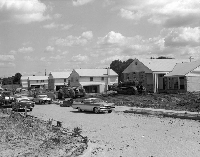 Historic 1950s black and white photo of unlandscaped tract housing under construction.