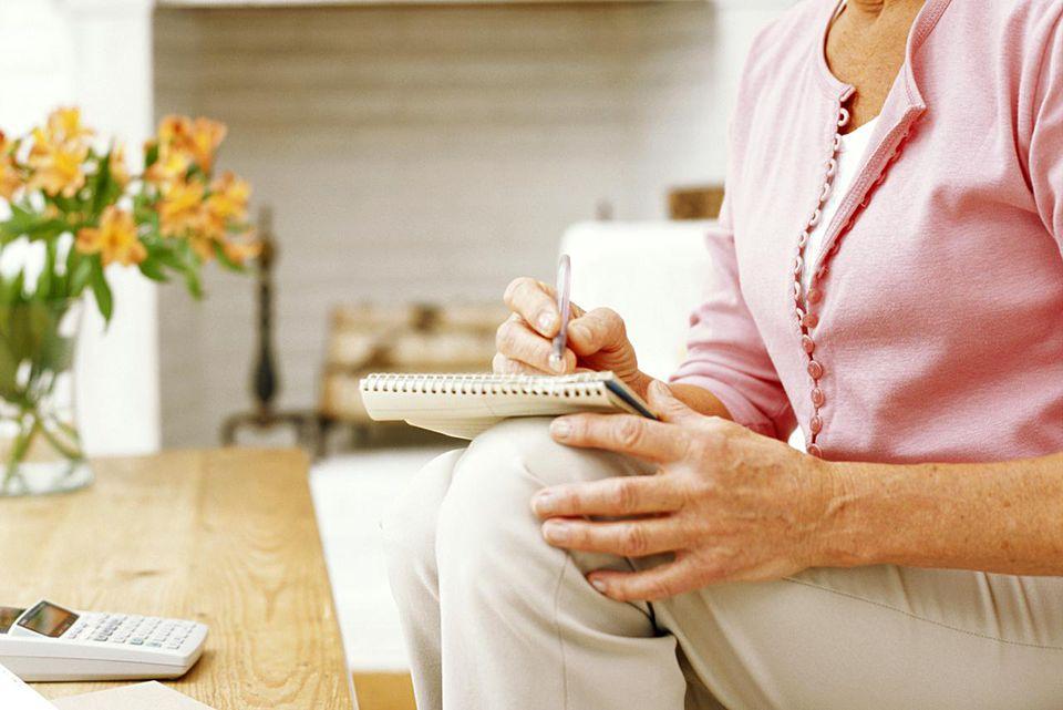 Senior woman sitting on sofa writing on notebook