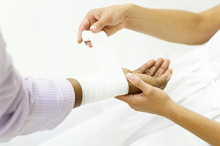 Nurse wrapping bandage around patient's wrist,close-up on hands