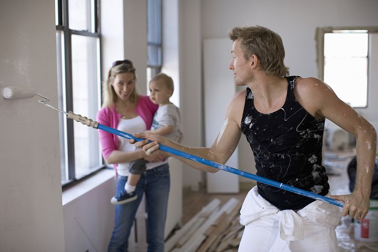 man painting walls while woman and child look on