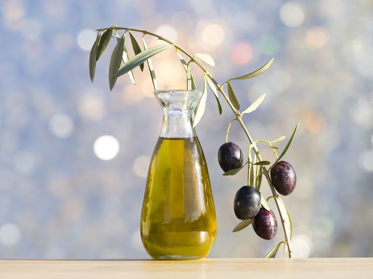 Glass oil extra virgin olive oil and a sprig of olive and green olives