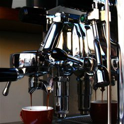 An image of an espresso machine group head with portafilter locked in place.