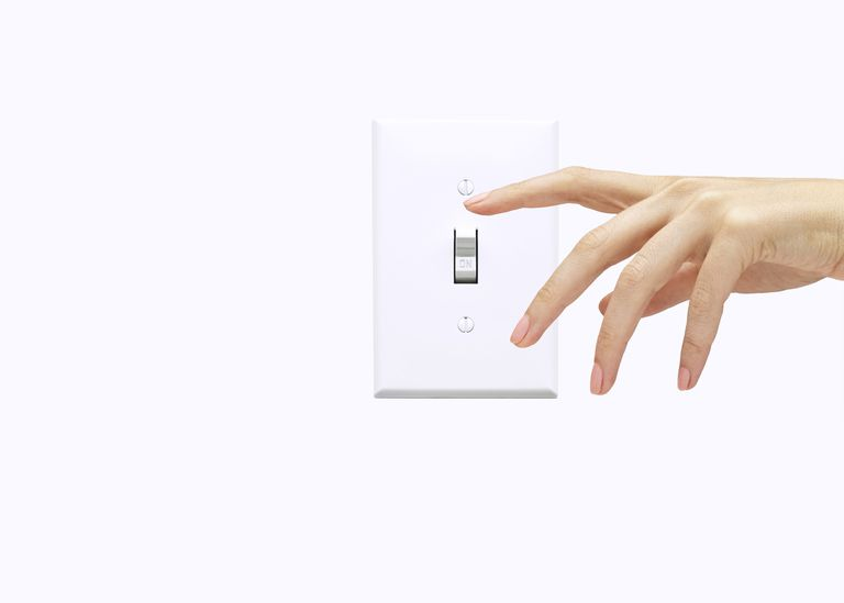 Hand of woman pressing light switch
