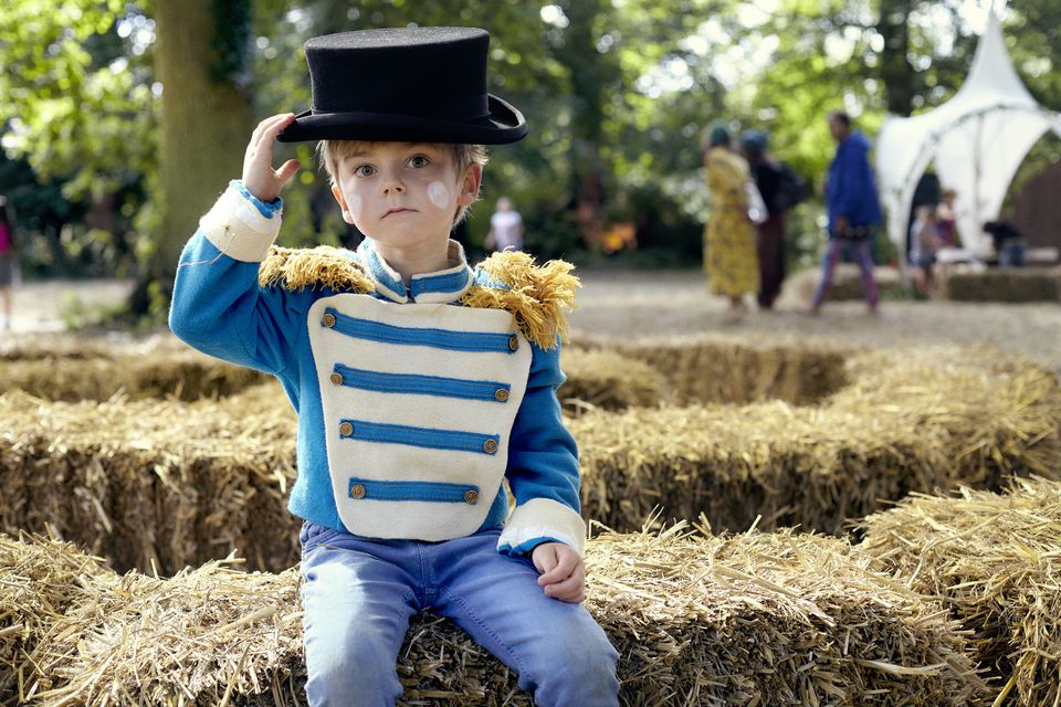 boy in fancy dress sitting on a hay bale