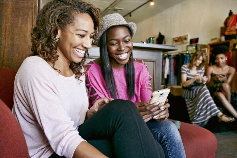 Women using cell phone in store