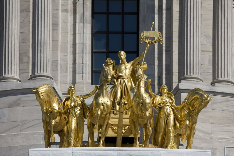 Gold sculpture of man with staff in a chariot pulled by four horses, dome pillars in the background