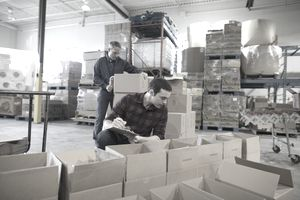 Male volunteer with clipboard checking donation boxes in warehouse