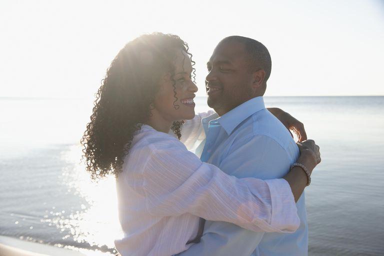 Black couple embracing on beach