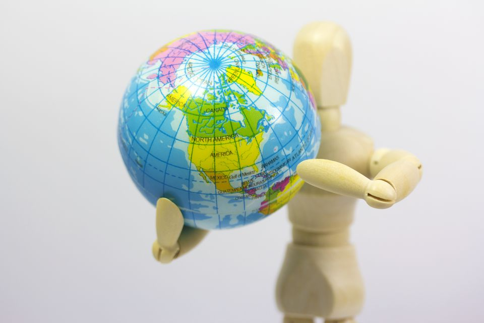 Articulated doll holding a globe.