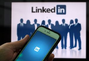 person holding smartphone with LinkedIn logo