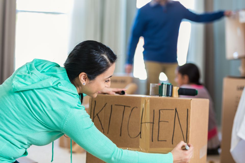 Woman labels box with kitchen items for move