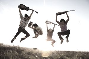 Caucasian men jumping with musical instruments
