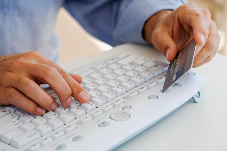 Man typing on computer keyboard, holding credit card, close-up, elevated view