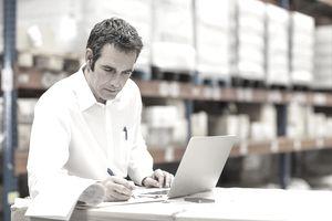 man working at laptop in warehouse