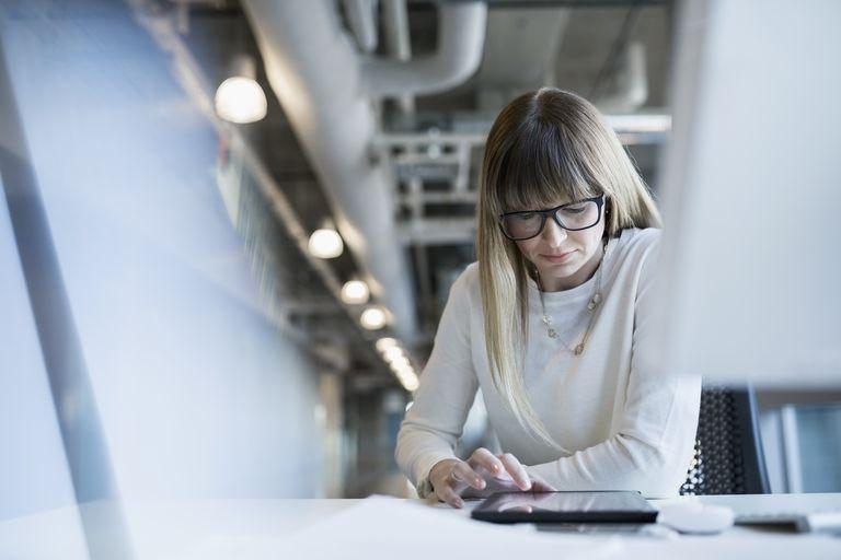Businesswoman using digital tablet at office desk