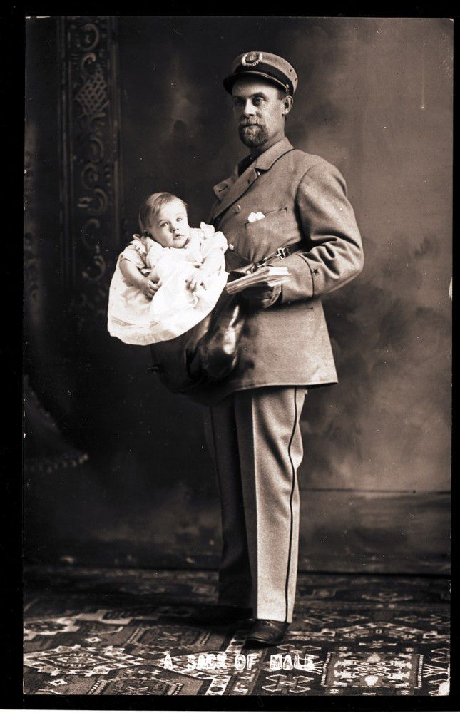 A US postman carrying a baby boy along with his letters.
