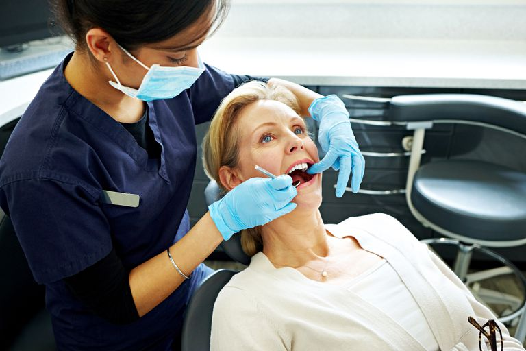 Mature woman having her teeth checked by dentist