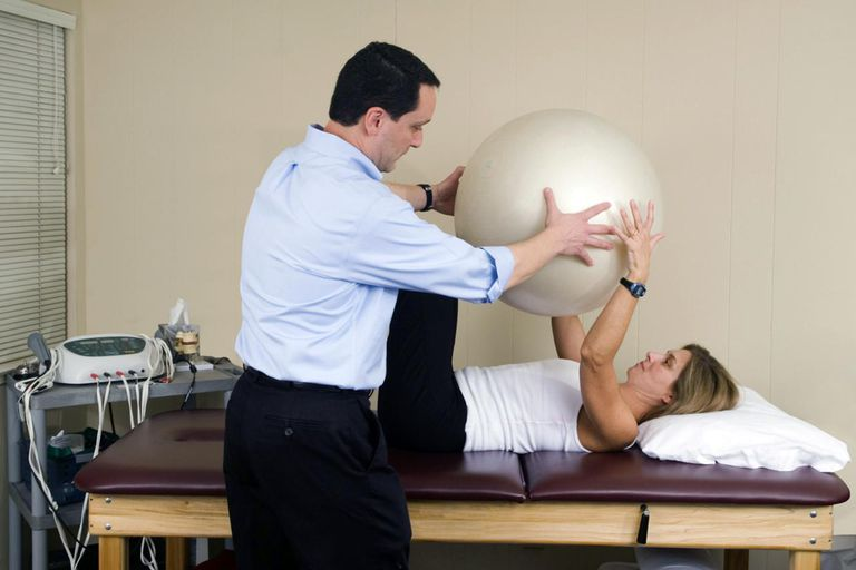 'Physical therapist helping his patient with a fitness ball, for back and abs stability work.Click below for a lightbox of all of my Physical Therapy and Chiropractic Treatment images:'