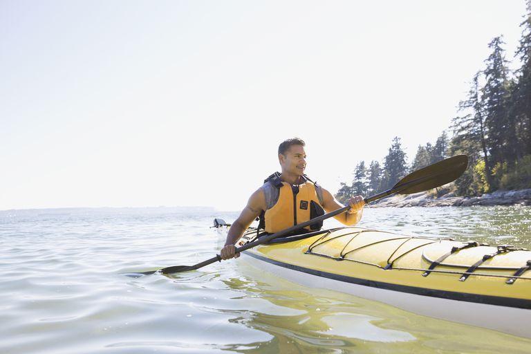Man kayaking on sunny ocean