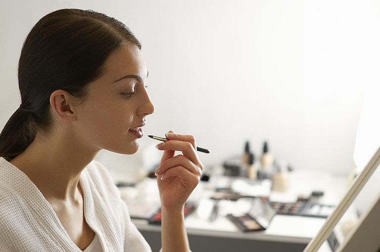 Woman applying make up with products in background
